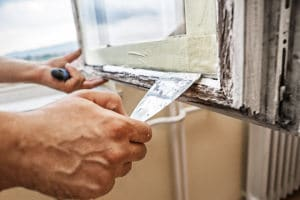 Image of a person cauking a window for weatherization