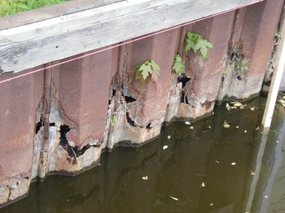 Photo of a rusted and cracked seawall.