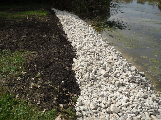 An image showing a rip rap retaining wall made of smaller rocks along a recently excavated shoreline.