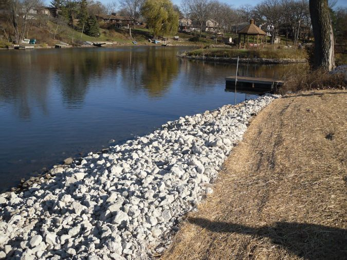 A rip rap retaining wall sits on a shoreline next to a lake leading up to a dock.