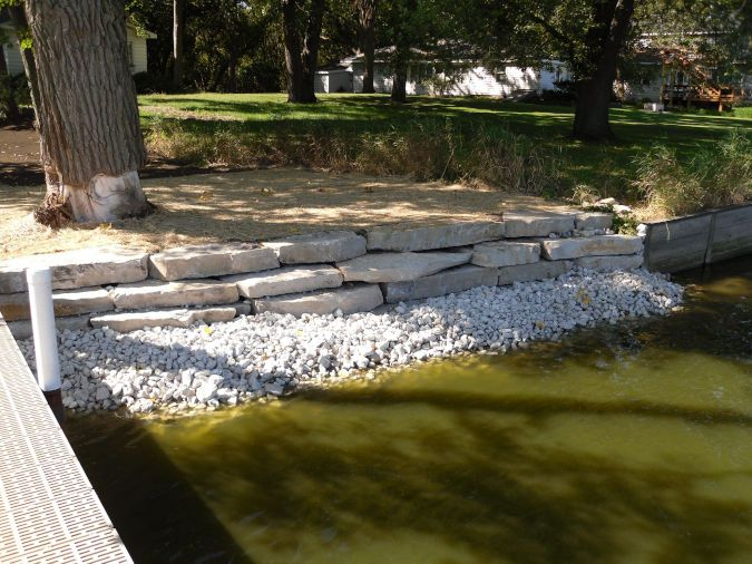 An image showing an outcropping retaining wall sits on top of rip rap next to a body of water.